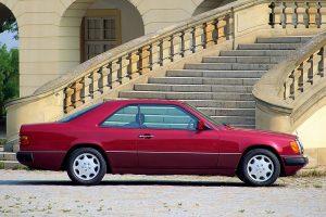 Une Mercedes 300 CE rouge de profil devant l'escalier d'un bâtiment
